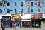 A man jogs in front of closed-off store fronts Sunday, March 29, 2020, in the Venice Beach section of Los Angeles. With cases of coronavirus surging and the death toll increasing, lawmakers are pleading with cooped-up Californians to spend a second weekend at home to slow the spread of the infections. (AP Photo/Marcio Jose Sanchez)