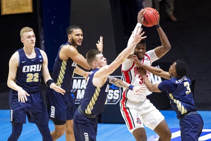 Ohio State's E.J. Liddell, second from right, gets pressure from Oral Roberts' Francis Lacis (22), Kevin Obanor, second from left, Carlos Jürgens, center, and Max Abmas (3) during the second half of a first-round game in the NCAA men's college basketball tournament, Friday, March 19, 2021, at Mackey Arena in West Lafayette, Ind. Oral Roberts won in overtime. (AP Photo/Robert Franklin)
