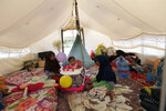 In this Monday, April 1, 2019, photo, children play inside a tent at a camp for those affected by the Sept. 28, 2018, earthquake and liquefaction in Palu, Central Sulawesi, Indonesia. Six months after the city was ripped apart by an earthquake, tsunami and liquifying soil that sucked neighborhoods into the earth, thousands of people are living in sweltering tent cities and almost a third of temporary housing is unoccupied after aid groups and authorities failed to connect it to water or electricity. (AP Photo/Tatan Syuflana)