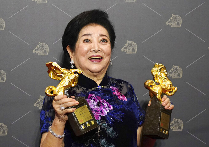 """Taiwanese actress Chen Shu-fang holds her awards for Best Leading Actress and Best Supporting Actress at the 57th Golden Horse Awards in Taipei, Taiwan, Saturday, Nov. 21, 2020. Chen won for the film """"Dear Tenant"""" at this year's Golden Horse Awards - one of the Chinese-language film industry's biggest annual events. (AP Photo/Billy Dai)"""