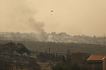 A helicopter drops water onto an advancing wildfire, in the town of Damour, just over 15km (9 miles) south of Beirut, Lebanon, Tuesday, Oct. 15, 2019. Strong fires spread in different parts of Lebanon forcing some residents to flee their homes in the middle of the night as the flames reached residential areas in villages south of Beirut. (AP Photo/Hassan Ammar)