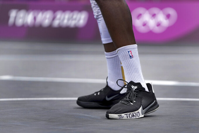 """Poland's Michael Hicks has """"Tokyo"""" written on his shoe during a men's 3-on-3 basketball game against Latvia at the 2020 Summer Olympics, Saturday, July 24, 2021, in Tokyo, Japan. (AP Photo/Jeff Roberson)"""