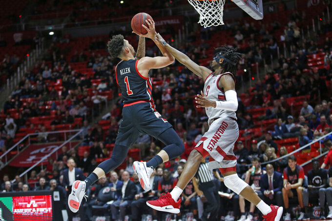 Stanford guard Daejon Davis, right, fouls Utah forward Timmy Allen (1) as he goes to the basket in the second half during an NCAA college basketball game Thursday, Feb. 6, 2020, in Salt Lake City. (AP Photo/Rick Bowmer)