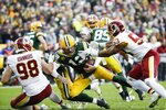 Green Bay Packers' Aaron Rodgers is sacked by Washington Redskins' Jon Bostic (53) and Matthew Ioannidis (98) during the second half of an NFL football game Sunday, Dec. 8, 2019, in Green Bay, Wis. The Packers won 20-15. (AP Photo/Mike Roemer)