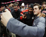 Georgia quarterback Jacob Eason takes a photo with a fan during media day, Saturday, Jan. 6, 2018, in Atlanta. Georgia and Alabama will be playing for the NCAA football national championship on Monday, Jan. 8. (AP Photo/John Bazemore)
