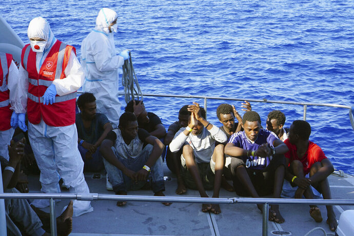 Migrants are evacuated by Italian Coast guards from the Open Arms Spanish humanitarian boat at the coasts of the Sicilian island of Lampedusa, southern Italy, Saturday, Aug. 17, 2019. Italy's hard-line interior minister buckled under pressure Saturday and agreed to let 27 unaccompanied minors leave a migrant rescue ship after two weeks at sea, temporarily easing a political standoff that has threatened the viability of the populist government. (AP Photo/Francisco Gentico)
