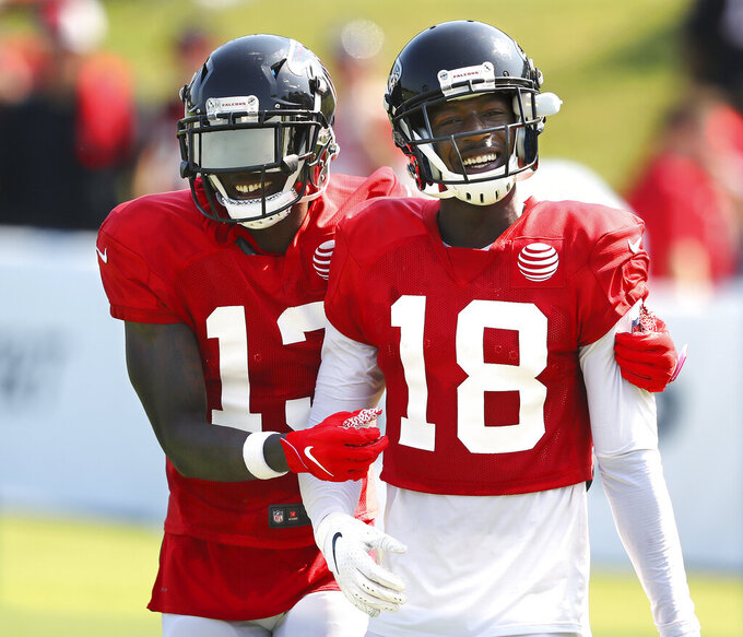 Atlanta Falcons wide receiver Calvin Ridley (18) gets some encouragement from wide receiver Christain Blake after catching a pass during an NFL football team practice in Flowery Branch, Ga., Monday, July 29, 2019. (Curtis Compton/Atlanta Journal-Constitution via AP)