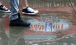 The Food City logo is reflected from the official pace car as people walk past in the rain before a NASCAR Cup Series auto race, Sunday, April 15, 2018 in Bristol, Tenn. (AP Photo/Wade Payne)