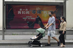 """Residents pass by a government propaganda with the words """"Our Carbon Zero Agreement"""" on a street of in Beijing, China on Aug. 30, 2021. Chinese and U.S. officials plan to talk this week about reducing pollution by the world's two largest economies, an area of potential cooperation between two governments whose relations are strained on other issues. (AP Photo/Ng Han Guan)"""