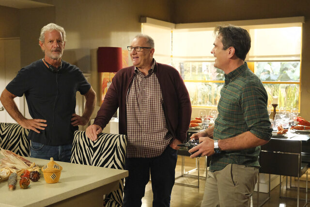This image released by ABC shows, from left, executive producer Christopher Lloyd, and actors Ed O'Neill and Ty Burrell on the set of