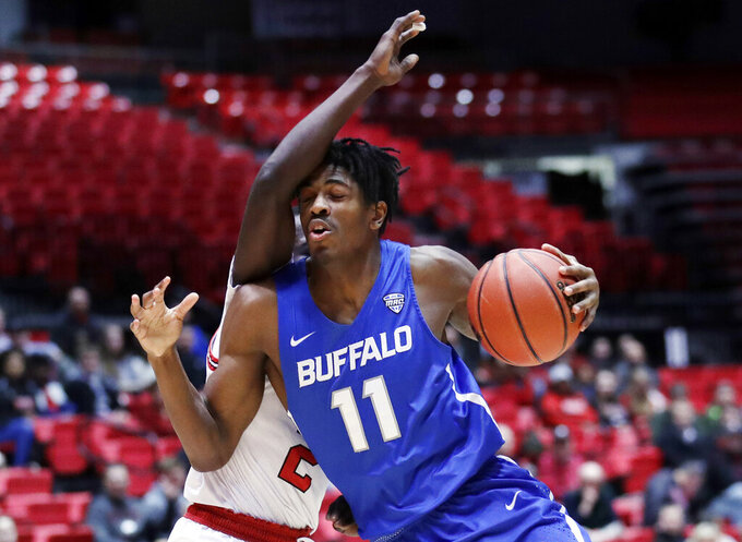 Buffalo forward Jonathan Williams, right, drives against Northern Illinois guard Gairges Daow during the first half of an NCAA college basketball game Tuesday, Jan. 22, 2019, in DeKalb, Ill. (AP Photo/Nam Y. Huh)