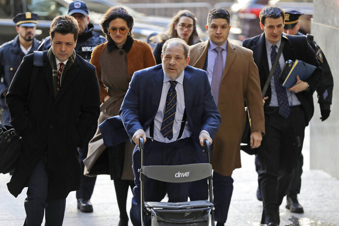 Harvey Weinstein, center, arrives at a Manhattan courthouse for his rape trial in New York, Friday, Feb. 14, 2020. (AP Photo/Seth Wenig)