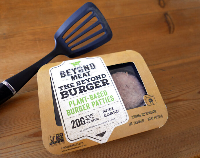 FILE - In this June 26, 2019, file photo, a package of meatless burgers by Beyond Meat are seen in Orlando, Fla. More people are throwing plant-based burgers on the grill this summer. Beyond Meat, which makes pea protein-based burgers and sausages, says its second-quarter revenue in 2020 jumped 69% to $113 million as more households tried its products. That far outpaced Wall Street's forecast of $99 million. (AP Photo/John Raoux, File)