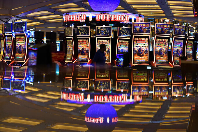 A person walks through a casino area ahead of the opening of Resorts World Las Vegas, Wednesday, June 23, 2021, in Las Vegas. Even the chips have chips at the newest casino resort on the Las Vegas Strip. When Resorts World Las Vegas opens to guests and gamblers late Thursday, card players will bet with house chips implanted with sensors at tables that take cashless transactions and track every bet, split, double-down and side wager. (AP Photo/John Locher)