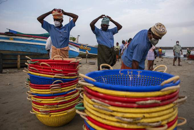 Laborers wearing masks as a precaution against COVID-19 get ready to collect fish from a fishing boat on the Arabian Sea coast in Kochi, Kerala state, India, Monday, Sept.20, 2021. The tiny southern state continues to battle the highest number of coronavirus cases in the country. (AP Photo/R S Iyer)