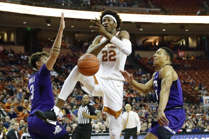 Texas forward Kai Jones (22) loses control of the ball as he drives to the basket against TCU guard Francisco Farabello (3) and guard Desmond Bane (1) during the second half of an NCAA college basketball game in Austin, Texas, Wednesday, Feb. 19, 2020. (AP Photo/Eric Gay)