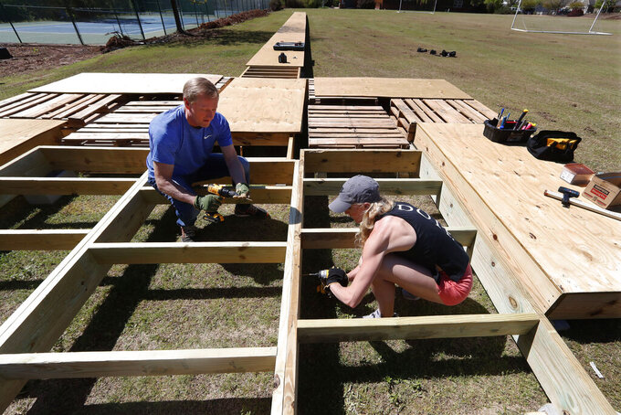 Olympic pole vaulting silver medalist Sandi Morris works on vaulting pit she is building with her father, Harry Morris, left, in Greenville, S.C., Tuesday, April 4, 2020.  (AP Photo/John Bazemore)