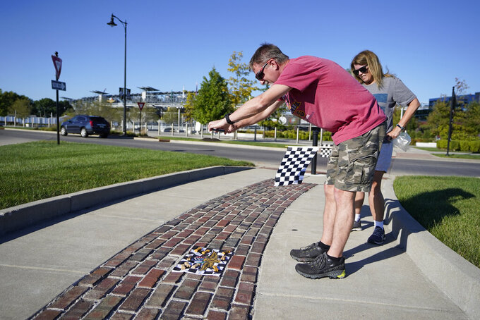 John and Susan Skelton take a photo of a race flag outside of the Indianapolis Motor Speedway, Thursday, Aug. 20, 2020, in Indianapolis. (AP Photo/Darron Cummings)
