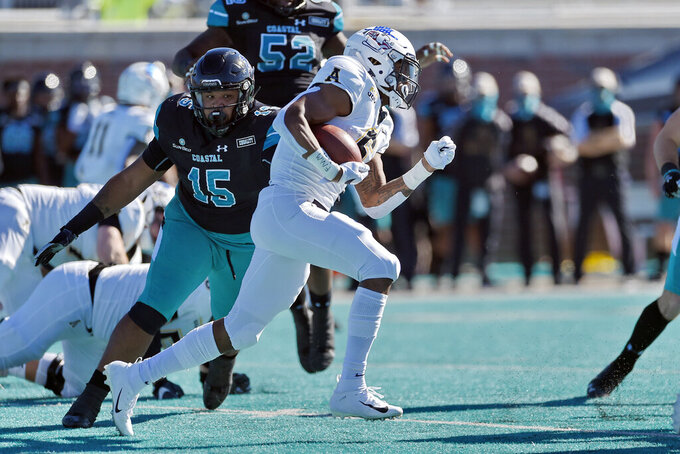 Appalachian State's Camerun Peoples, center, rushes while defended by Coastal Carolina's Jerrod Clark (15) during the first half of an NCAA college football game, Saturday, Nov. 21, 2020, in Conway, S.C. (AP Photo/Richard Shiro)