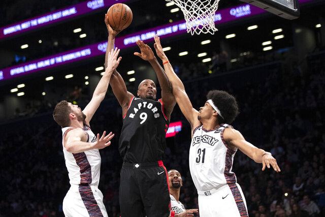 Toronto Raptors forward Serge Ibaka (9) goes to the basket between Brooklyn Nets center Jarrett Allen (31) and guard Joe Harris during the first half of an NBA basketball game Saturday, Jan. 4, 2020, in New York. (AP Photo/Mary Altaffer)