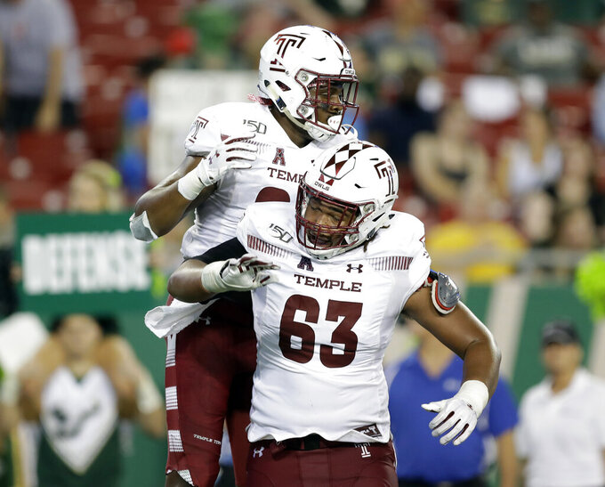 Temple tight end Kenny Yeboah (84) celebrates with offensive lineman Isaac Moore (63) after catching a 1-yard touchdown pass against South Florida during the first half of an NCAA college football game Thursday, Nov. 7, 2019, in Tampa, Fla. (AP Photo/Chris O'Meara)