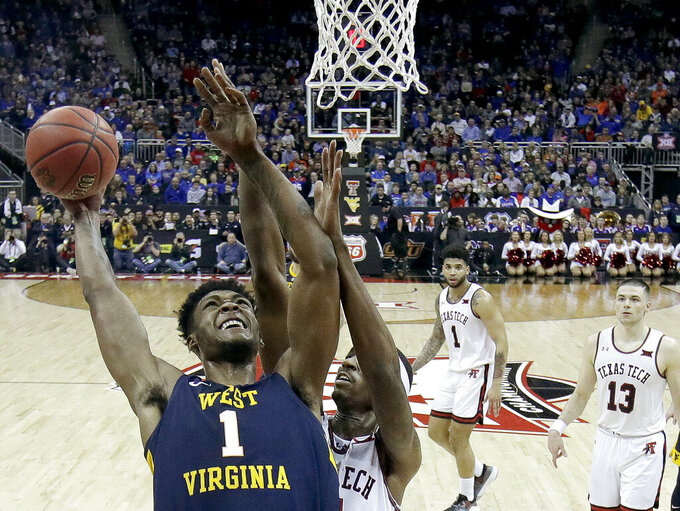 West Virginia's Derek Culver (1) shoots under pressure from Texas Tech's Tariq Owens during the second half of an NCAA college basketball game in the Big 12 men's tournament Thursday, March 14, 2019, in Kansas City, Mo. West Virginia won 79-74. (AP Photo/Charlie Riedel)