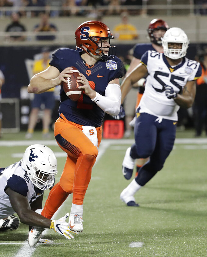Syracuse quarterback Eric Dungey, center, scrambles as he is pressured by West Virginia defensive lineman Ezekiel Rose, left, and defensive lineman Dante Stills (55) during the first half of the Camping World Bowl NCAA college football game Friday, Dec. 28, 2018, in Orlando, Fla. (AP Photo/John Raoux)