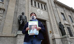 FILE - In this June 10, 2020 file photo, member of Noi Denunceremo (We will denounce) Facebook group, Laura Silvestri holds up a photograph of her father Giuseppe, a COVID-19 victim, in front of Bergamo's court, Italy, Wednesday, June 10, 2020. Noi Denunceremo and affiliated non-profit committee are filing 100 new cases Monday, July 13, 2020, with Bergamo prosecutors, on top of 50 complaints lodged last month.  (AP Photo/Antonio Calanni, file)