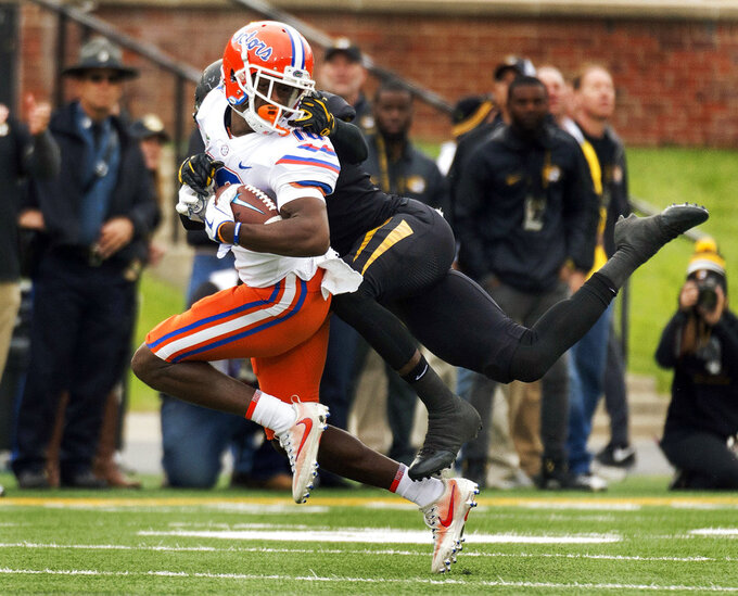 FILE - In this Nov. 4, 2017, file photo, Florida wide receiver Josh Hammond, left, is tackled by Missouri's DeMarkus Acy, right, as he grabs his face mask during the first half of an NCAA college football game in Columbia, Mo. No. 13 Florida is counting on a much better performance against Missouri this season. A lopsided loss to the Tigers was the low point for Florida in 2017. (AP Photo/L.G. Patterson, File)