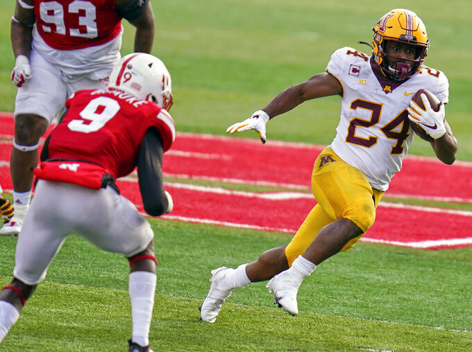 FILE - In this Dec. 12, 2020, file photo, Minnesota running back Mohamed Ibrahim (24) carries the ball away from Nebraska safety Marquel Dismuke (9) during the second half of an NCAA college football game in Lincoln, Neb. As college athletes like Ibrahim begin making money from the use of their names, images and likenesses, concerns are being raised over how the new rules will affect team chemistry. (AP Photo/Nati Harnik, File)
