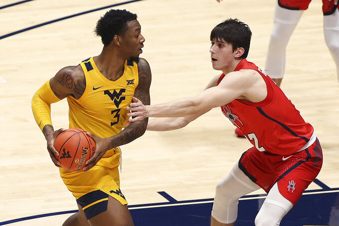 West Virginia forward Gabe Osabuohien (3) is defended by Richmond guard Andre Gustavson (22) during the second half of an NCAA college basketball game Sunday, Dec. 13, 2020, in Morgantown, W.Va. (AP Photo/Kathleen Batten)