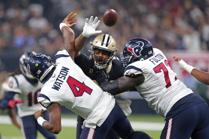 New Orleans Saints defensive end Cameron Jordan tries to bat down a pass by Houston Texans quarterback Deshaun Watson (4) as offensive guard Zach Fulton blocks in the first half of an NFL football game in New Orleans, Monday, Sept. 9, 2019. (AP Photo/Bill Feig)