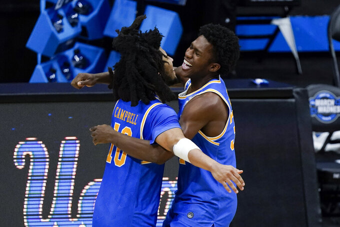 UCLA Bruins guard Tyger Campbell (10) and David Singleton (34) celebrate after an Elite 8 game against Michigan in the NCAA men's college basketball tournament at Lucas Oil Stadium, Wednesday, March 31, 2021, in Indianapolis. UCLA won 51-49. (AP Photo/Michael Conroy)