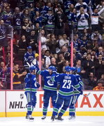 Vancouver Canucks' Bo Horvat, Josh Leivo, Alexander Edler, of Sweden, and Brock Boeser celebrate Horvat's goal against the Ottawa Senators during the first period of an NHL hockey game Wednesday, March 20, 2019, in Vancouver, British Columbia. (Darryl Dyck/The Canadian Press via AP)