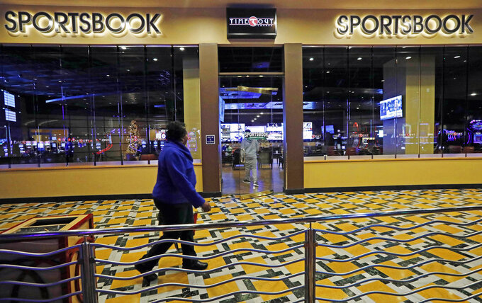 In this Dec. 18, 2018 photo, a woman walks by the Time Out Lounge at the Pearl River Resort, in Philadelphia, Miss. The sports book owned by the Mississippi Band of Choctaw Indians is the first to open on tribal lands outside of Nevada following a U.S. Supreme Court ruling earlier this year, a no-brainer business decision given the sports fans among its gambling clientele. (AP Photo/Rogelio V. Solis)
