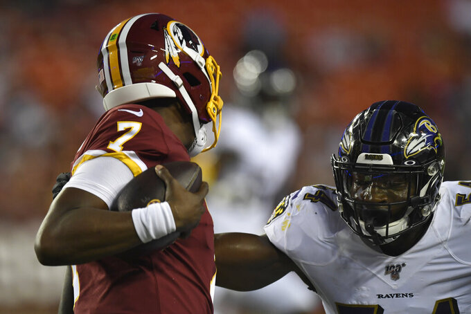 Baltimore Ravens linebacker Tyus Bowser, right, eyes the ball as Washington Redskins quarterback Dwayne Haskins (7) looks for an opening during the first half of an NFL preseason football game at FedEx Field in Landover, Md., Thursday, Aug. 29, 2019. (AP Photo/Susan Walsh)