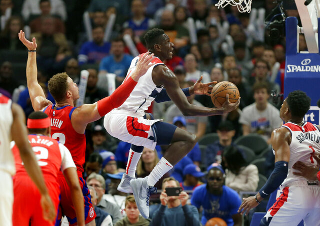 Washington Wizards guard Isaac Bonga, center, goes to the basket past Detroit Pistons forward Blake Griffin (23) during the first half of an NBA basketball game Thursday, Dec. 26, 2019, in Detroit. (AP Photo/Duane Burleson)