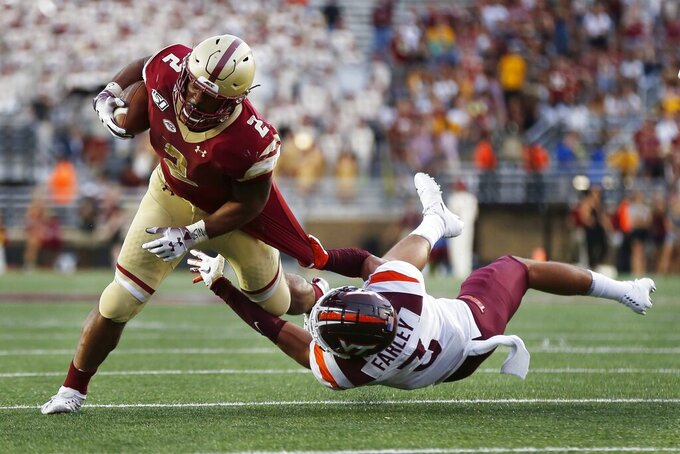 Boston College running back AJ Dillon (2) breaks tackle on Virginia Tech defensive back Caleb Farley (3) during the second half of an NCAA college football game in Boston, Saturday, Aug. 31, 2019. (AP Photo/Michael Dwyer)