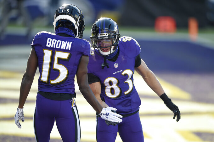 Baltimore Ravens wide receiver Marquise Brown (15) is congratulated by wide receiver Willie Snead (83) after catching a touchdown pass from quarterback Lamar Jackson, not visible, during the first half of an NFL football game against the New York Giants, Sunday, Dec. 27, 2020, in Baltimore. (AP Photo/Gail Burton)