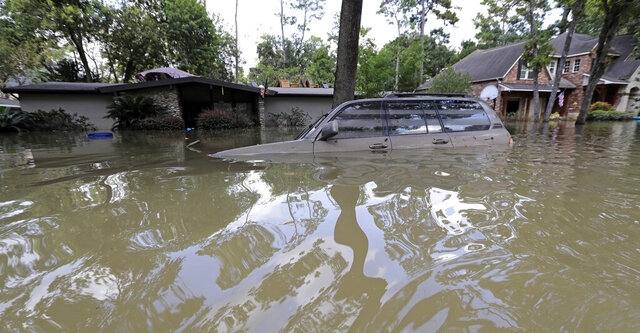 FILE - In this Sept. 4, 2017, file photo, a vehicle is submerged in floodwater in the aftermath of Hurricane Harvey in Houston. Senior U.S. Judge Charles Lettow in Washington. D.C. ruled Tuesday, Dec. 17, 2019, the U.S. Army Corps of Engineers is liable for damages to a group of Houston-area homes and businesses flooded by two federally owned reservoirs during Hurricane Harvey because the inundation was due to how the federal government built and maintained the dams. (AP Photo/David J. Phillip, File)
