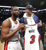 Miami Heat guard Dwyane Wade, left, poses with former NBA player Carmelo Anthony, after giving Anthony his game jersey following the Heat's NBA basketball game against the Brooklyn Nets on Wednesday, April 10, 2019, in New York. (AP Photo/Kathy Willens)