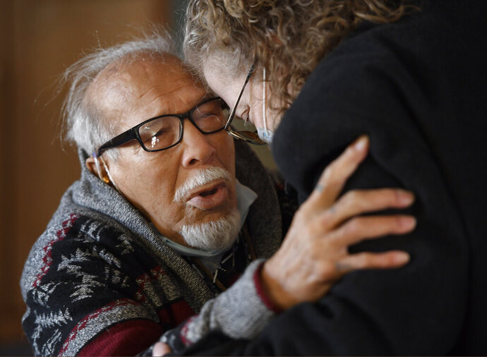 Anthony Martinez, left, embraces his niece, Kelly Brasier, at the Logan County Northeast Colorado Health Department building while trying to secure Anthony's birth certificate Friday, Jan. 15, 2021 in Sterling, Colo. Anthony Martinez, 84, suffering from dementia, was released from the Sterling Correctional Facility Friday after serving over 30-years in prison burglary and habitual offenses, Governor Polis commuted his sentence. Kelly is taking her uncle to Pennsylvania to take care of him. (Andy Cross/The Denver Post via AP)
