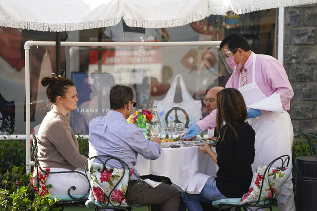 Diners are served outside by a waiter wearing a mask, face shield and rubber gloves, Wednesday, Nov. 18, 2020, in the West Hollywood area of Los Angeles. Los Angeles County imposed new restrictions on businesses Tuesday and is readying plans for a mandatory curfew for all but essential workers if coronavirus cases keep spiking. (AP Photo/Ashley Landis)