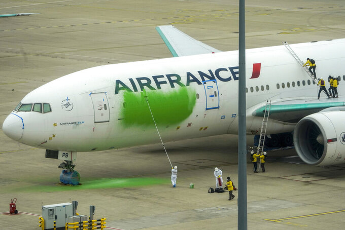 In this photo provided by Greenpeace, Greenpeace activists paint a side of an Air France Boeing 777, which was parked without passengers, Friday March 5, 2021 at Roissy airport, north of Paris. Nine Greenpeace activists were arrested after vandalizing an Air France jet with green paint Friday as part of an eco-protest that raised serious concerns about airport security. (Denis Meyer/Greenpeace via AP)