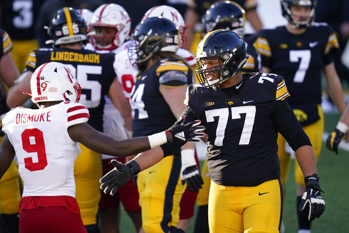 Iowa offensive lineman Alaric Jackson (77) greets Nebraska safety Marquel Dismuke (9) after an NCAA college football game, Friday, Nov. 27, 2020, in Iowa City, Iowa. Iowa won 26-20. (AP Photo/Charlie Neibergall)