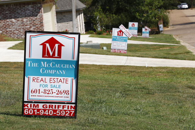 FILE - In this Sept. 25, 2019 file photo, a realty company's signs rest on several lawns in front of newly constructed houses in Brandon, Miss..  Long-term U.S. mortgage rates fell, Thursday, June 18, 2020,  as the benchmark 30-year home loan reached a new all-time low. Mortgage buyer Freddie Mac reports that the average rate on the key 30-year loan declined to 3.13% from 3.21% last week.  (AP Photo/Rogelio V. Solis, File)