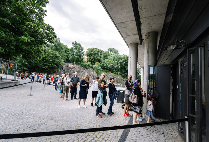 Visitors queue outside the Vasa Museum in Stockholm, Wednesday July 15, 2020. The museum reopened Wednesday after closing due to the COVID-19 pandemic. (Stina Stjernkvist/TT via AP)