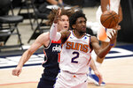 Phoenix Suns guard Langston Galloway (2) reaches for the ball in front of Washington Wizards center Robin Lopez, back, during the first half of an NBA basketball game, Monday, Jan. 11, 2021, in Washington. (AP Photo/Nick Wass)