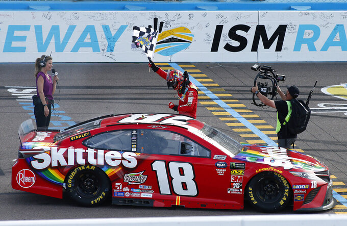 Kyle Busch waves the checkered flag after winning the NASCAR Cup Series auto race at ISM Raceway, Sunday, March 10, 2019, in Avondale, Ariz. (AP Photo/Ralph Freso)