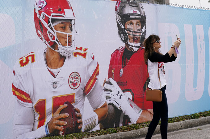Kansas City Chiefs fan Tracey Brasabr takes a selfie in front of Raymond James Stadium ahead of Super Bowl 55 Saturday, Feb. 6, 2021, in Tampa, Fla. The venue is hosting Sunday's Super Bowl football game between the Tampa Bay Buccaneers and the Kansas City Chiefs. (AP Photo/Charlie Riedel)